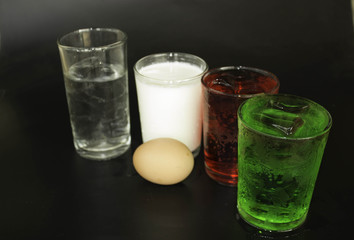 Red and green eggs and milk in a glass on a black background.