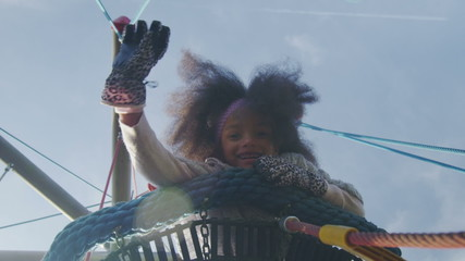 Little girl waving to camera in slow motion on a climbing frame