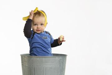 Grappig kind in de vuilbak met banaan