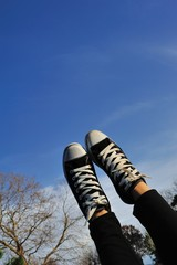 sneakers on blue sky with woman foot