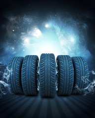 Wedge of new car wheels. Background is night sky and stripes at