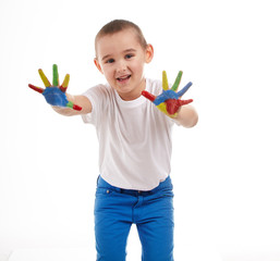 Five year old boy with hands painted in colorful paints ready fo