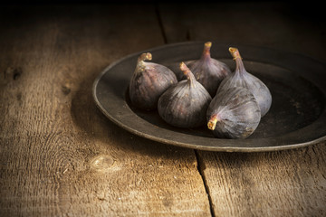 Fresh figs in moody natural lighting set with vintage retro styl