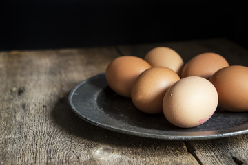 Fresh eggs on pewter plate in vintage retro style natural lighti