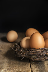 Fresh eggs in birds nest in vintage retro style moody natural li