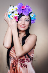 Beautiful woman in the studio with a wreath of flowers on her he