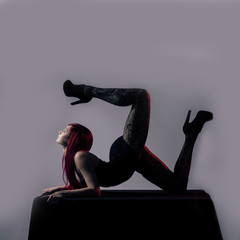 Beautiful red haired woman acrobat over grey background