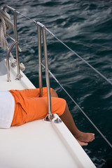 Young boy sitting on yacht side