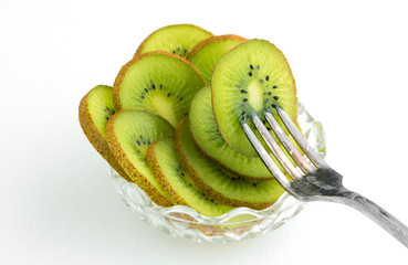 Bowl of kiwi with fork stuck in fruit