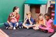Gruppe Kinder mit Bilderbuch im Kindergarten