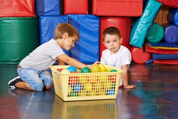 Kinder räumen Bälle auf in Turnhalle