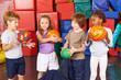 Kinder spielen mit Bällen in Turnhalle