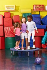 Kinder springen gemeinsam auf Trampolin