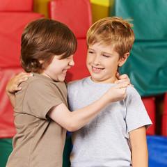 Zwei lachende Jungs haben Spaß in Turnhalle