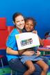 Mädchen und Kindergärtnerin zeigen Bild
