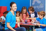 Fototapety Frau als Kindergärtnerin mit Gruppe Kinder
