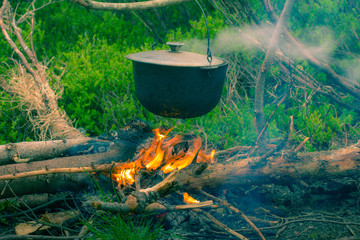 Boiling pot on the campfire on picnic.