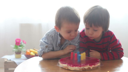 Two boys, blowing candels on birthday cake