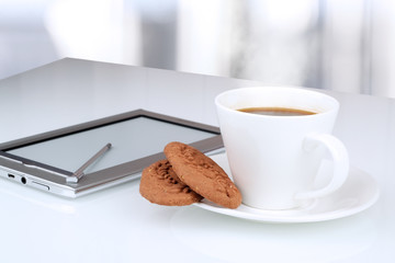 Close up image of cup of coffee with cookies. digital tablet on
