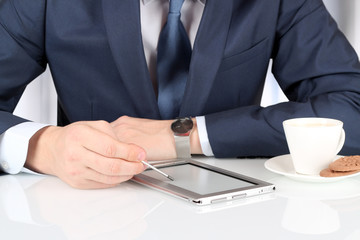 business man working with a digital tablet.  Сup of coffee wit
