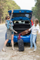 Mother and daughter traveling by car with suitcases.