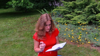 Pregnant business woman write on paper notebook sit on grass