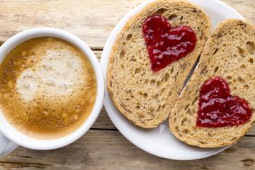 Fresh coffee. Grain slice of bread with jam heart shape.