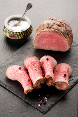 Roast beef with salt and pepper on stone board