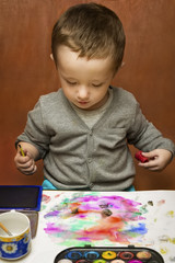 Adorable little baby boy looking concentrated at his painting on