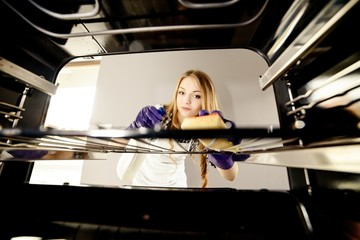 close up of woman hand cleaning oven at home kitchen