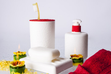 Toothbrushes, soap, liquid soap and red towel on white backgroun