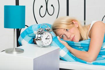 Frau hat Schlafprobleme und schaut auf den Wecker