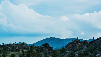 Running clouds and mountain silhouette of rocks and trees, TimeL