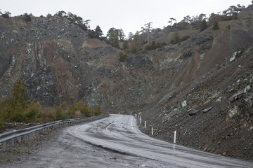 Asphalt road in the mountains. Winter. Rain