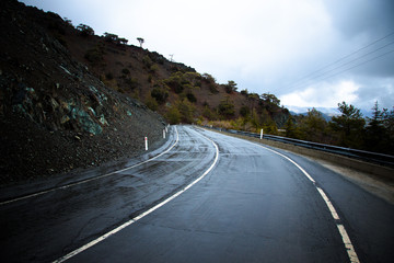 Asphalt road in the mountains. Winter. Rain. Toned