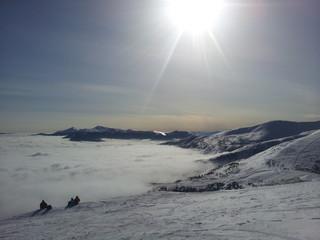 Just sun shining above foggy mountain top