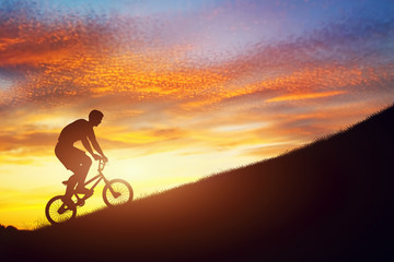 Man riding a bmx bike uphill against sunset sky. Challenge. © Photocreo Bednarek