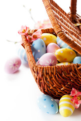 Easter decoration: colorful eggs in basket on white