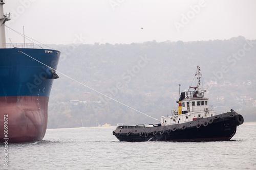 ugboat assisting huge vessel - 80690672