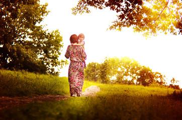 Светлый путь материнства, мама с ребенком идут по дороге