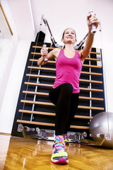 Beautiful woman doing exercise on kinesis machine.