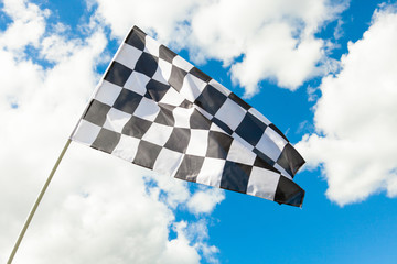 Checkered flag waving in the wind - clouds on background