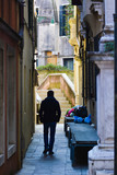 Man walking on Venice traditional small stree in Italy