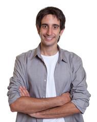 Lachender Mann im grauen Hemd mit verschränkten Armen