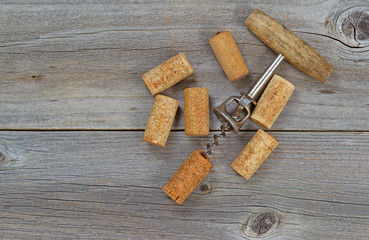 Several Used Wine Corks and Opener on Wood