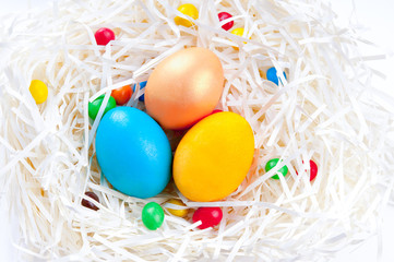 Colorful Easter eggs in nest on white background