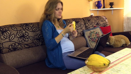 pregnant woman chat on internet, eat banana, relax with laptop