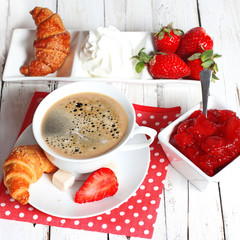 breakfast with croissants, strawberry  and cup of coffee on whit