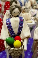Female handmade cornhusk figure holding basket with easter eggs