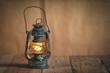 vintage kerosene oil lantern lamp burning with a soft glow light - 80697469